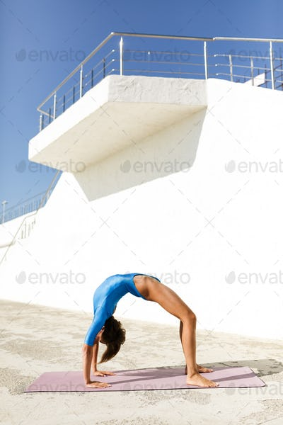 Woman with dark short hair in blue swimsuit doing yoga while standing on bridge pose
