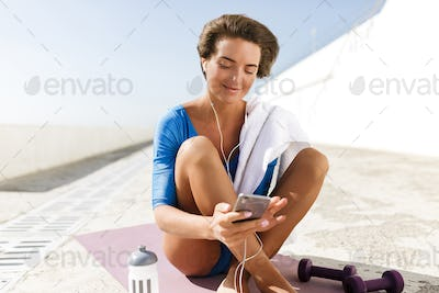Woman in blue swimsuit and earphones sitting on purple yoga mat and dreamily looking in cellphone