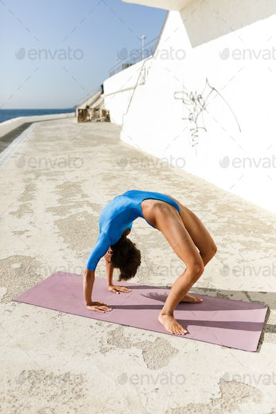 Pretty woman with dark short hair in blue swimsuit practicing yoga while standing on bridge pose