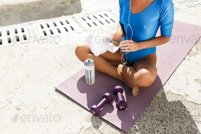 Woman body in blue swimsuit sitting on yoga mat in lotus pose with cellphone in hands