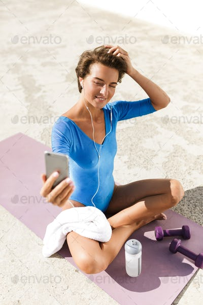 Smiling woman in blue swimsuit sitting on yoga mat and happily looking in her cellphone