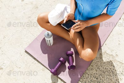 Photo of woman body in blue swimsuit sitting on yoga mat in lotus pose and using cellphone