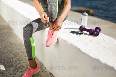 Woman hands and legs in pink sneakers sitting with purple dumbbells, cellphone and bottle of water