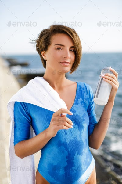 Woman in blue swimsuit with white towel on shoulder and bottle in hand dreamily looking in camera