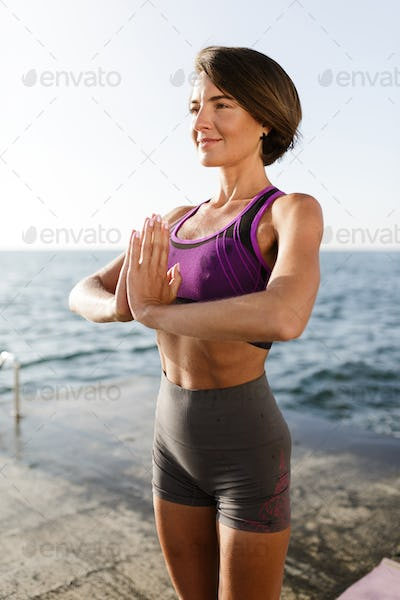 Portrait of lady in sporty top and shorts practicing yoga with sea view on background