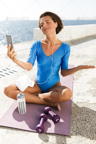 Beautiful woman in blue swimsuit sitting on yoga mat and dreamily looking in her cellphone