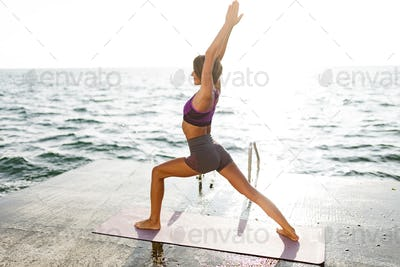 Woman with dark short hair standing and pulling her hands up while training yoga poses by the sea