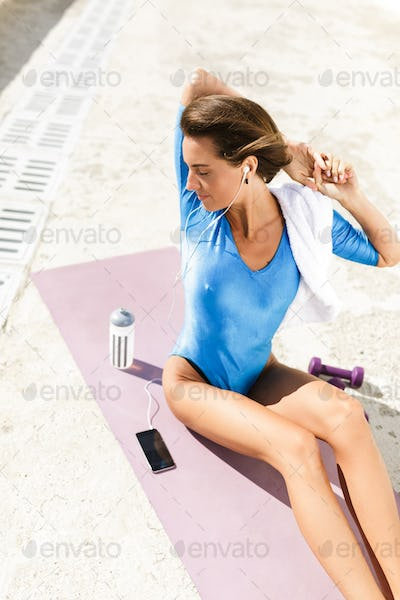 Woman with short hair in blue swimsuit sitting on purple yoga mat and thoughtfully looking aside