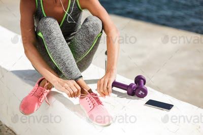 Woman hands and legs in pink sneakers sitting and tie shoelaces with purple dumbbells, cellphone