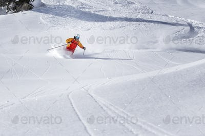 freeride skier skiing through the fresh powder snow
