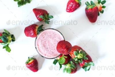 Strawberry milkshake with mint on a white background