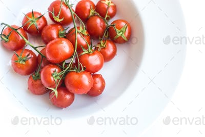 Ripe fresh red cherry tomatoes on a white background