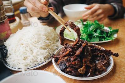 Eating Vietnamese bun cha with chopsticks