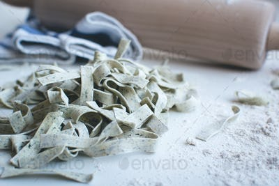 Pasta tagliatelle covered by flour with a wooden roller on a white background