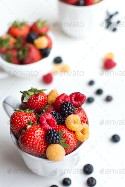 Vibrant shot of colorful healthy fresh berries in a cup on a white background