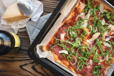 Homemade pizza prosciutto crudo and arugula
