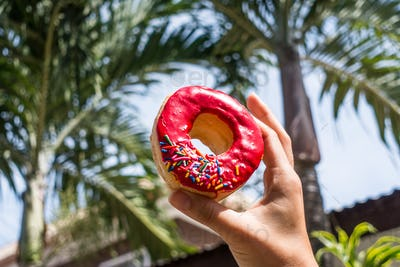 Holding donut near palm trees