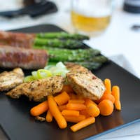 Chicken breasts steak with asparagus wrapped in bacon
