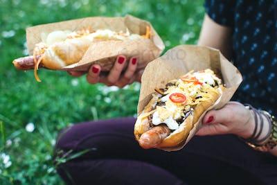 Sitting in grass and enjoying hot dog