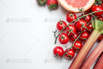 Red cherry tomatoes and rhubarb on a white background