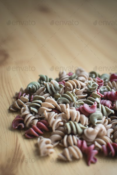 Colorful fusili pasta detail on a wooden background