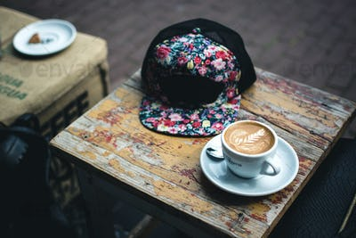 Hipster espresso macchiato with snapback on table
