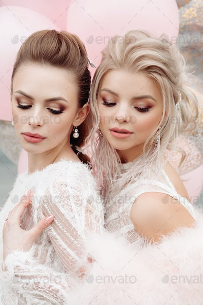 Two gorgeous models with make up and hairdo in white