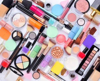 Makeup cosmetics, brushes and other makeup products on white bac