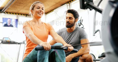 Personal trainer giving instructions a woman in gym