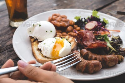 Filling brunch with poached eggs, beans, bacon, sausages and mushrooms