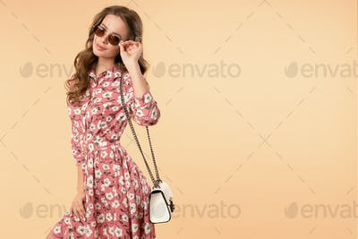 Sweet and charming girl in pretty summer dress with handbag and sunglasses