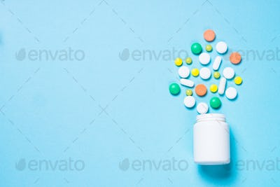 Pills, tablets and vitamin on blue