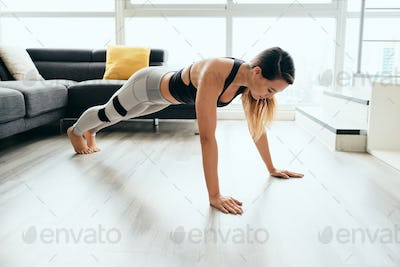 Woman Practicing Yoga At Home Doing Sun Salutation Routine