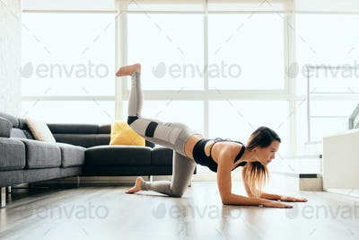 Adult Woman Training Legs and Back Doing Plank Donkey Kicks