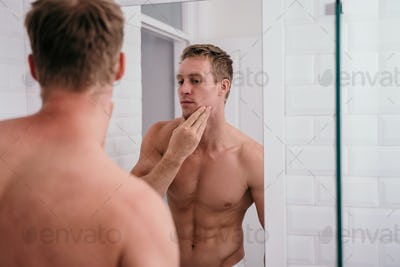Attractive muscular man preparing himself in front of mirror