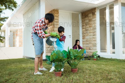father and son watering a plant in front of their house together