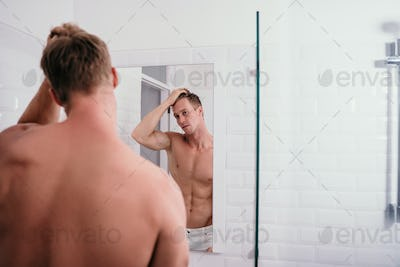 Portrait man muscle body at front reflection in the mirror