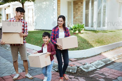 asian moving to new house carrying cardboard box