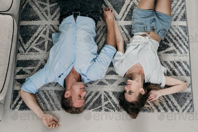 Affectionate couple lying and relaxing on the carpet