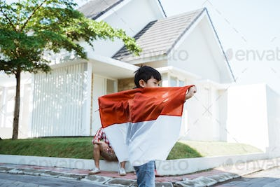 kid playing around holding indonesian flag