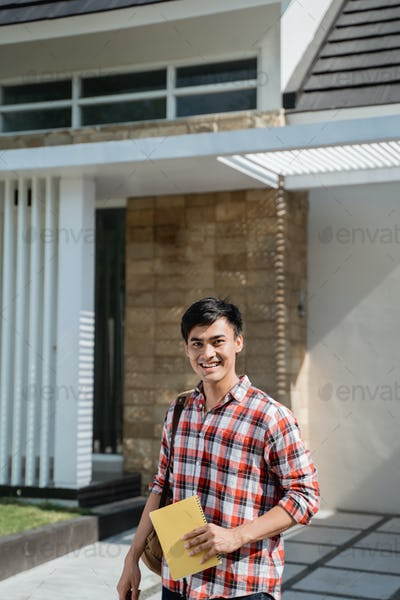 male student standing in front of his house