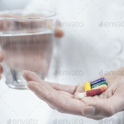 Hands with Colorful Pills and a Glass of Water