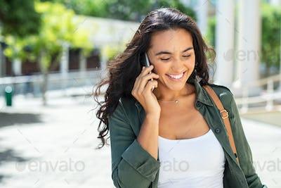 Latin smiling woman talking on phone