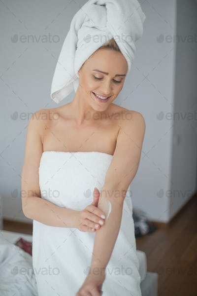 Middle aged beautiful blond woman moisturizes arm after the shower