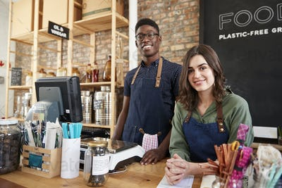 Portrait Of Male And Female Owners Of Sustainable Plastic Free Grocery Store Behind Sales Desk