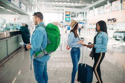 Three tourists receive a boarding pass in airport