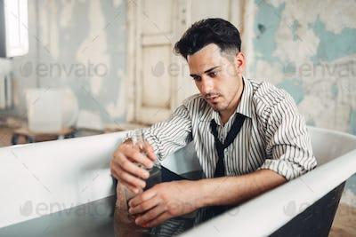 Drunk businessman in bathtub, suicide man concept