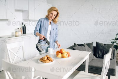 Happy woman cooking breakfast on the kitchen