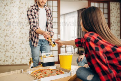 Friends with beer, pizza and popcorn at home party
