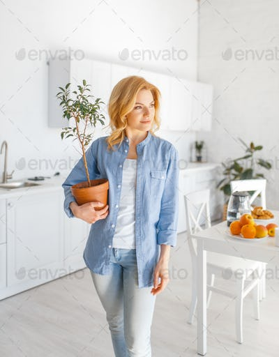 Young woman holds a flower in a pot on the kitchen